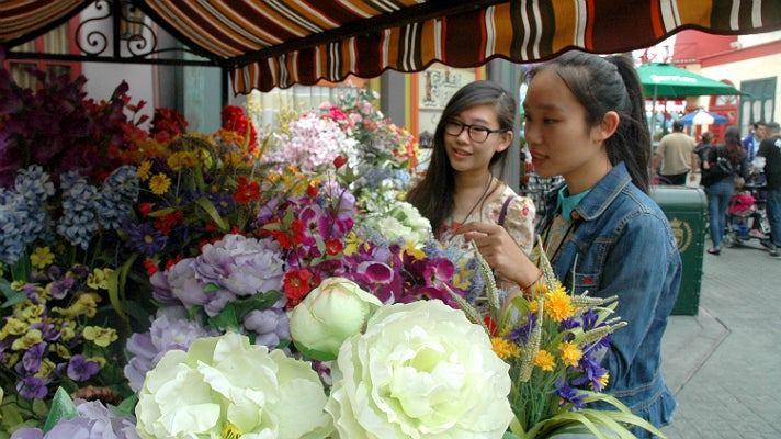 "Sally Guo and Susanna Niu admire the flowers in ""Paris"" at Universal Studios Hollywood"